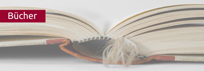 Ein dickes Buch liegt aufgeschlagen auf dem Tisch