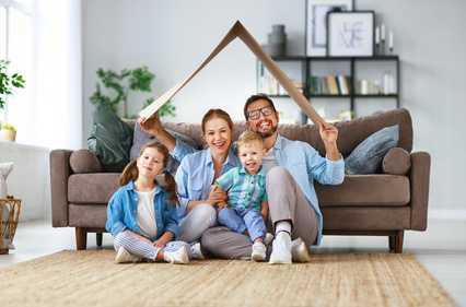 Familie mit zwei kleinen Kindern sitzt fröhlich auff dem Boden vor ihrer Couch