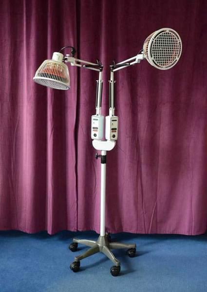 Vorschau: Eine weisse Stehlampe vor lila Hintergrund mit zwei Armen und zwei Therapieköpfen zur Abstrahlung der Infrarot Wärmelampe