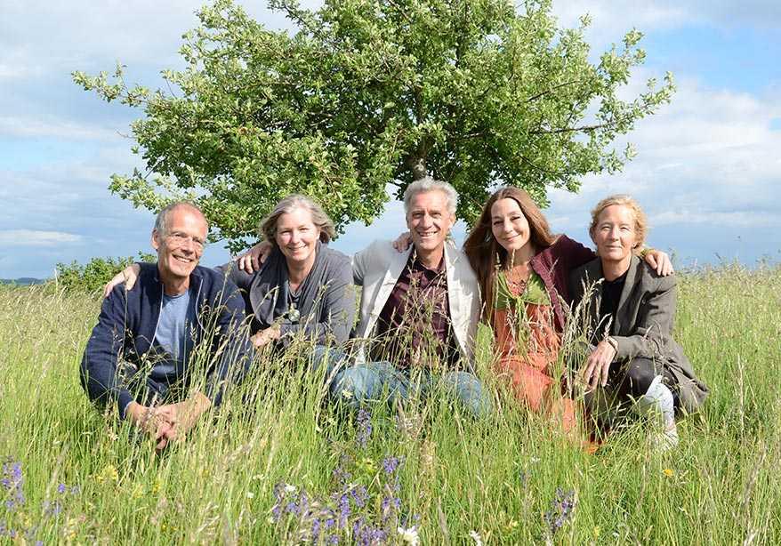 Fünf Menschen hocken auf einer Wiese mit hohem Gras, vor einem Apfelbaum und blauem Himmel