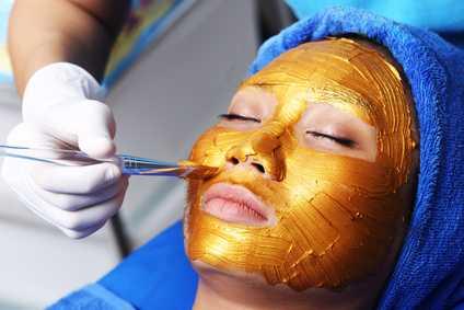 Auftragen von Gold auf das Gesicht einer Frau. Verjüngender Effekt von Goldkolloid