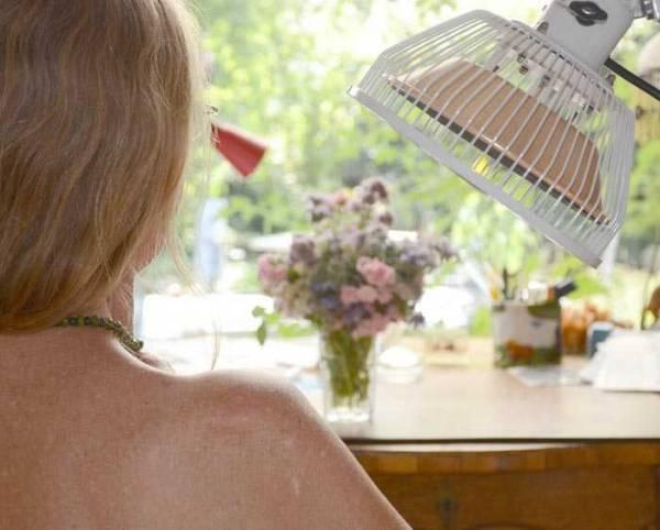 Vorschau:  Der Therapiekopf einer wärmenden Moxalampe mit Heilfrequenzen ist auf die Schulter einer Frau gerichtet.  Mit zwei Köpfen kann man zwei Bereiche gleichzeitig behandeln.