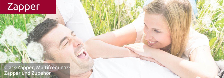 Ein glückliches Paar liegt im Gras und lacht. Sie sind gesund, weil sie den Zapper benützen.
