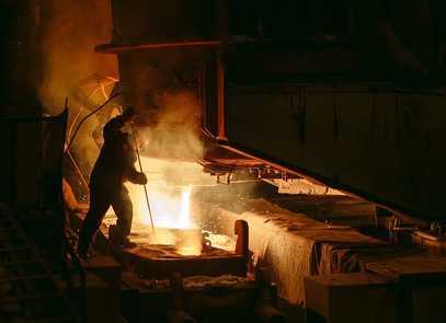 Ein Arbeiter rührt mit einem langen Stab in einer glühenden Masse