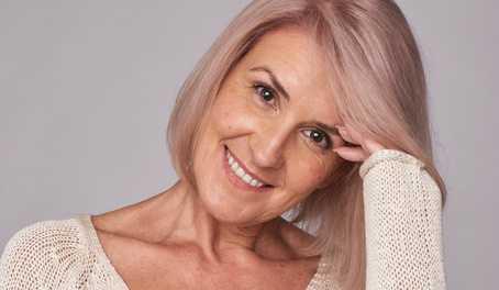 Lachende Frau mit circa 50 Jahren hält den Kopf schief