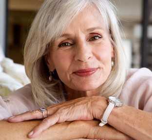 Eine hübsche, etwas 60jährige Frau mit grauen Haaren und braunen Augen lächelt in die Kamera