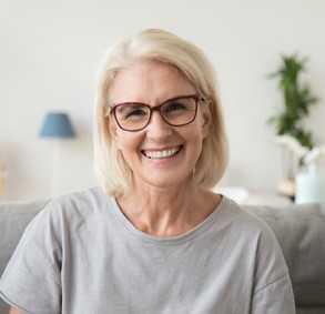 Ältere Frau mit langen, grauen Haaren und schwarzer Brille lächelt