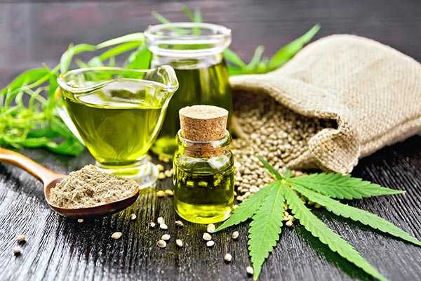 Cannabis-Blätter liegen auf einem grauen Holztisch neben einer Fiole mit grünen CBD-Öl, dahinter ein Leinensack mit Hanfsamen