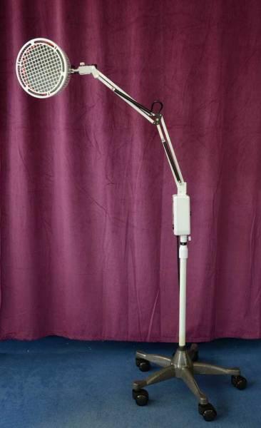 Vorschau: Eine weisse Stehlampe vor lila Hintergrund mit Therapiekopf zur Abstrahlung der heilenden Wärme
