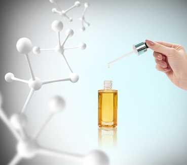 Moleküle mit 3 Armen schweben durch den Raum und eine Hand nimmt mit einer Pipette Öl aus einem Fläschchen