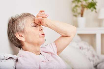 Eine Frau sitzt mit geschlossenen Augen auf dem Sofa und hält sich die Stirn