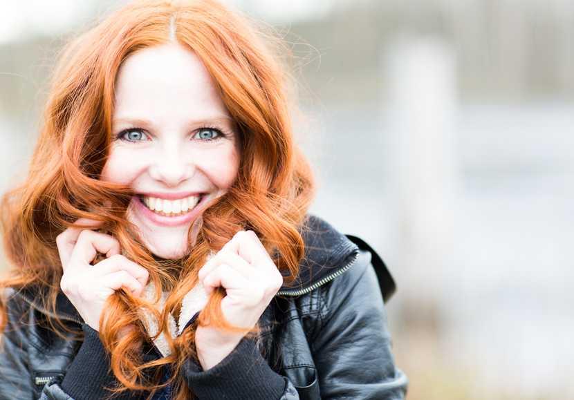 Lachende Frau fasst sich in ihre schönen, langen Haare
