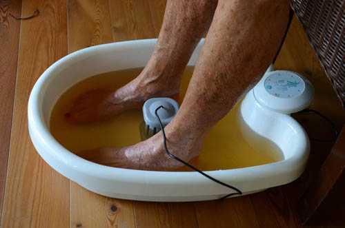 Zwei Beine stehen in einem Fußbad mit braunem Wasser