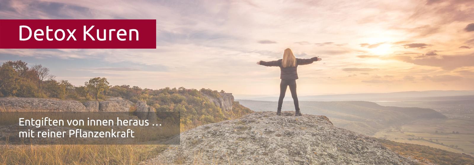 Frau steht mit ausgebreiteten Armen auf einem Berg und schaut auf den Sonnenuntergang in der Ferne