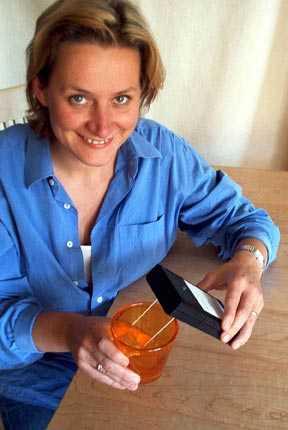Man sieht eine Frau, die das KoSi-Gerät auf ein Glas Wasser hält