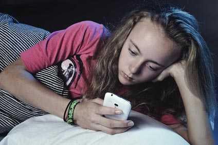 Ein Mädchen liegt am Abend mit ihrem Handy im Bett