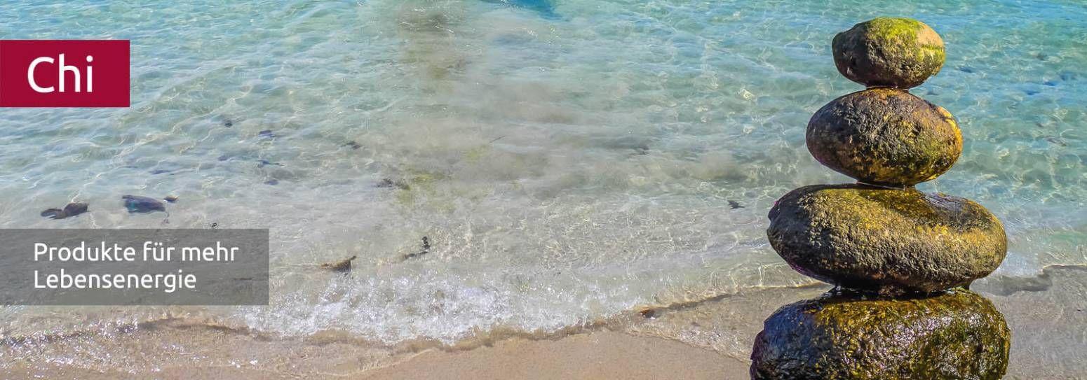 Strand mit klarem Wasser und gestapelten Steinen