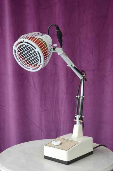 Eine weisse Tischlampe vor lila Hintergrund mit Therapiekopf zur Abstrahlung der heilenden Wärme