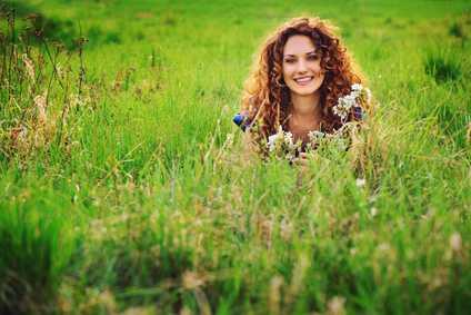 Eine gesunde, hübsche Frau liegt in einer Blumenwiese
