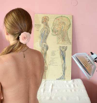 Man sieht den Rücken einer Frau, der von einem Lampenkopf bestrahlt wird. Im Hintergrund eine Akupunktur-Tafel