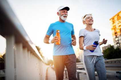 Ein älteres Paar joggt lächelnd durch eine Stadt